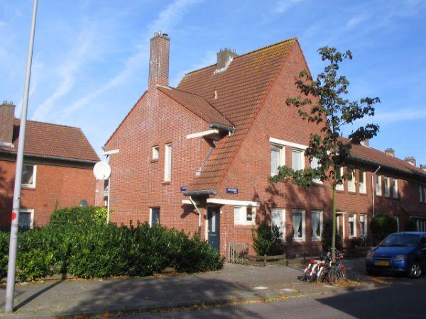 aanzicht kopgevel van een huizenblok in de latherusbuurt in amsterdam voor de renovatie met begroeiing naast het huis en een geparkeerde auto ervoor