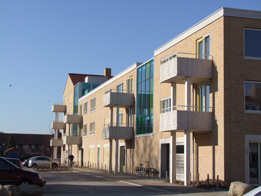 Zijaanzicht met uitstekende balkons van een van de gebouwen van de nieuwbouw in het schilderskwartier in woerden met gele en groene details