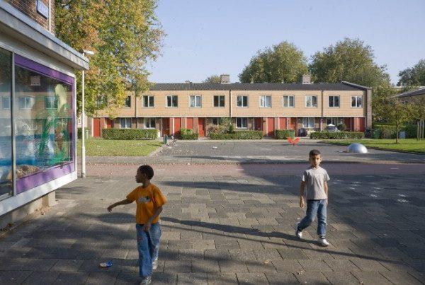 wijkaanzicht van de gerenoveerde woningen in de zierikzeebuurt met jongetjes op de voorgrond