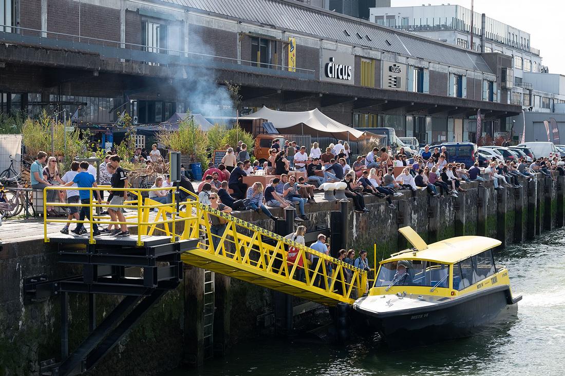 Mensen die op de kade zitten bij de fenix food factory op katendrecht in rotterdam tewrijl er een gele taxiboot aanmeert