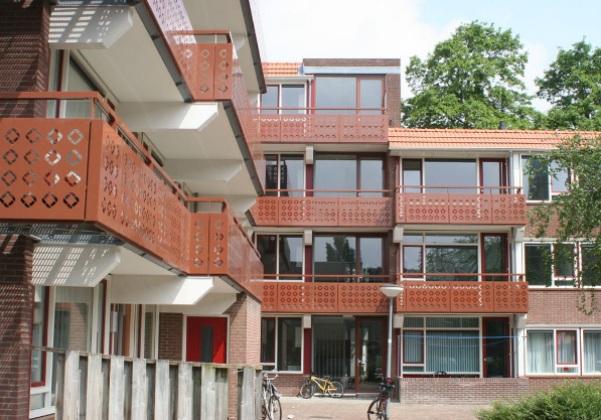aanzicht van de Van reynstraat in Rotterdam van een van de portiek en galerijen met bruine en rode accenten na de renovatie