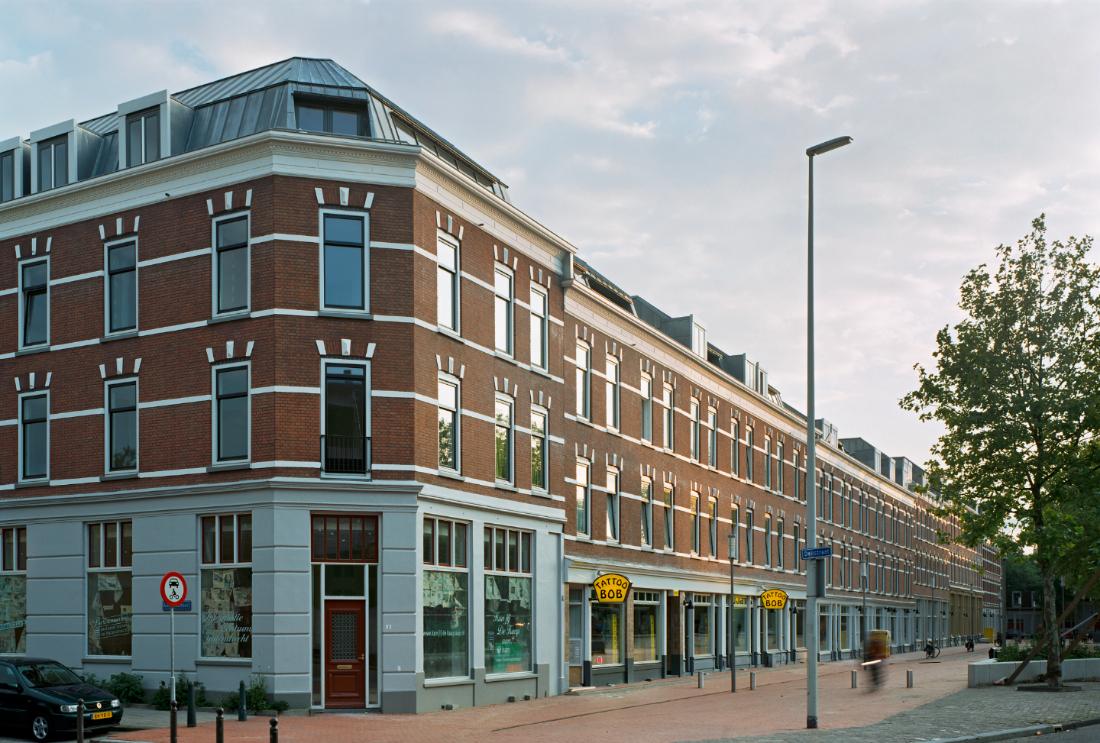 Foto van een deel van deliplein met in beeld tattoo bob en de gerenoveerde huizen aan de rand van het plein op katendrecht.