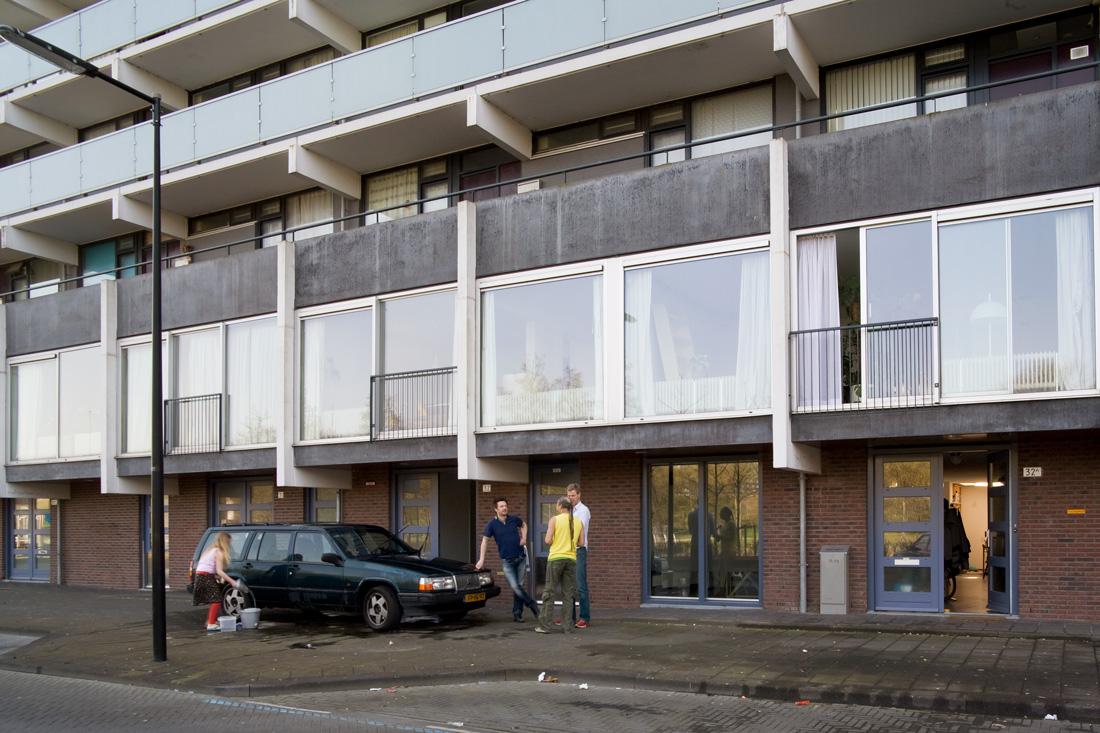 aangezicht van de plint van de gerenoveerde flats florijn in bijlmermeer met mensen op de stoep met een auto die gewassen wordt
