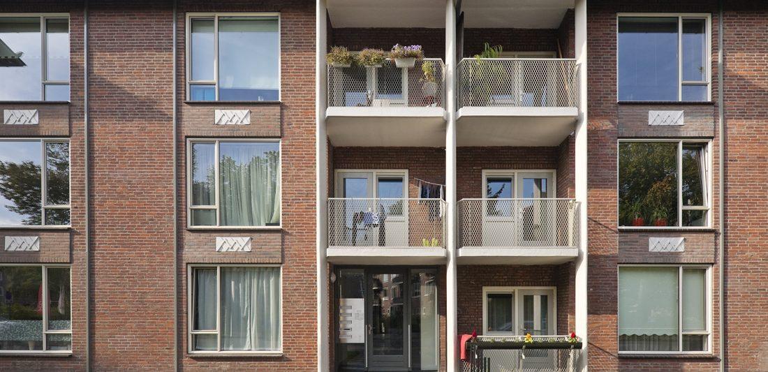 vooraanzicht van een van de gerenoveerde woonblokken aan de gasthuislaan in amersfoort met planten op de balkons