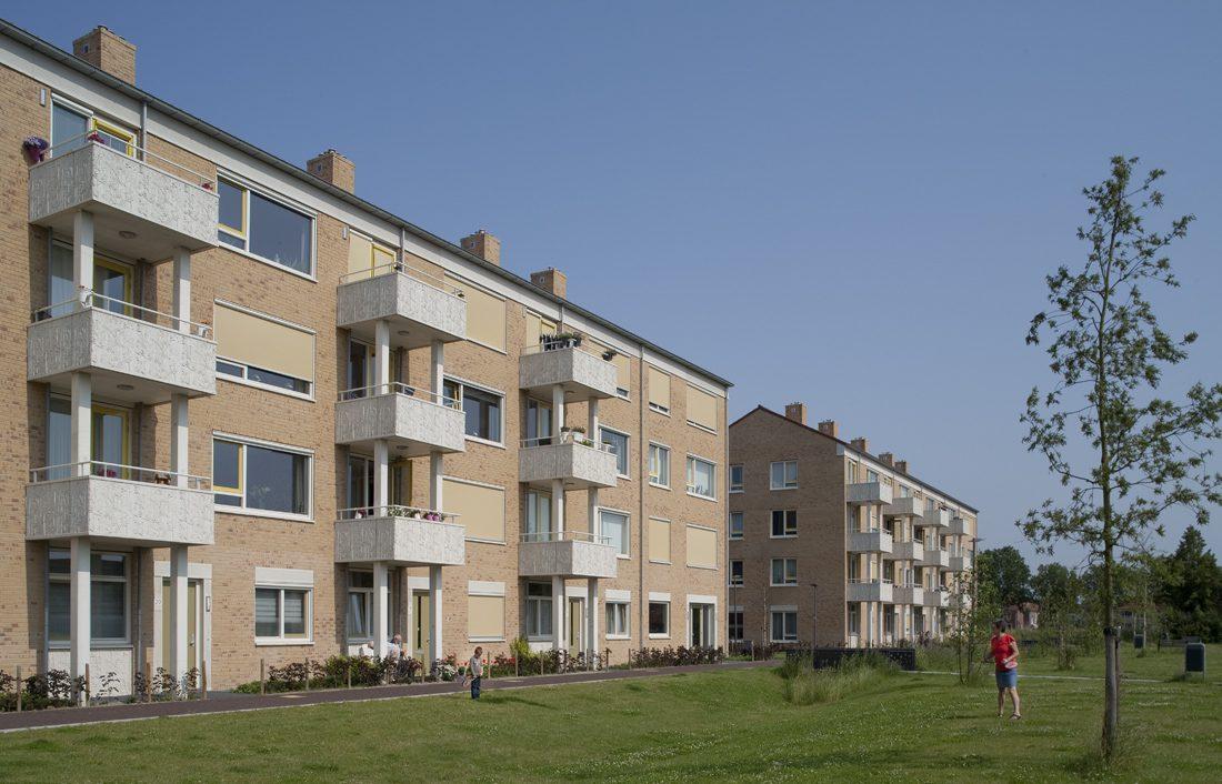 Zijaanzicht met uitstekende balkons van een van de gebouwen van de nieuwbouw in het schilderskwartier in woerden en mensen die spelen