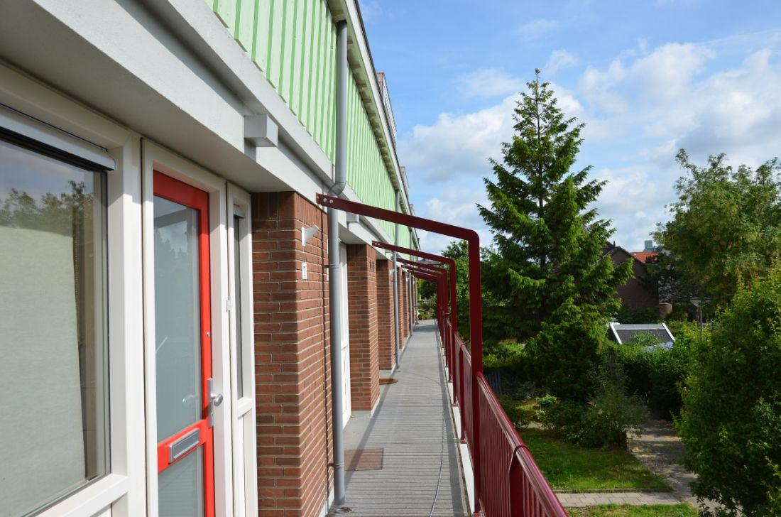 de galerij van een van de huizenblokken in de sagenbuurt in rotterdam na renovatie met rode reling