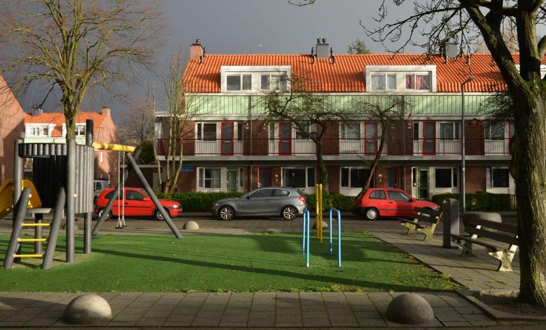 Een speeltuin met daarachter auto's en een vooraanzicht van gerenoveerde huizenblokken in de Sagenbuurt in Rotterdam