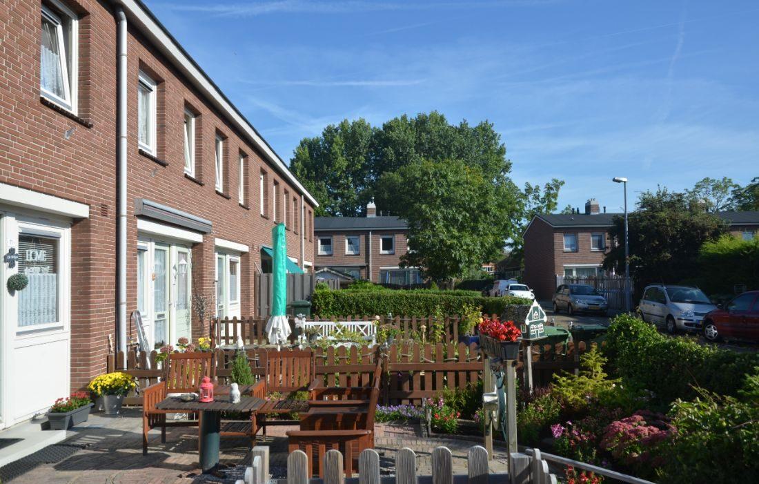 Zijaanzicht van een van de huizenblokken in de sagenbuurt in Rotterdam met bloemen en planten in de tuinen