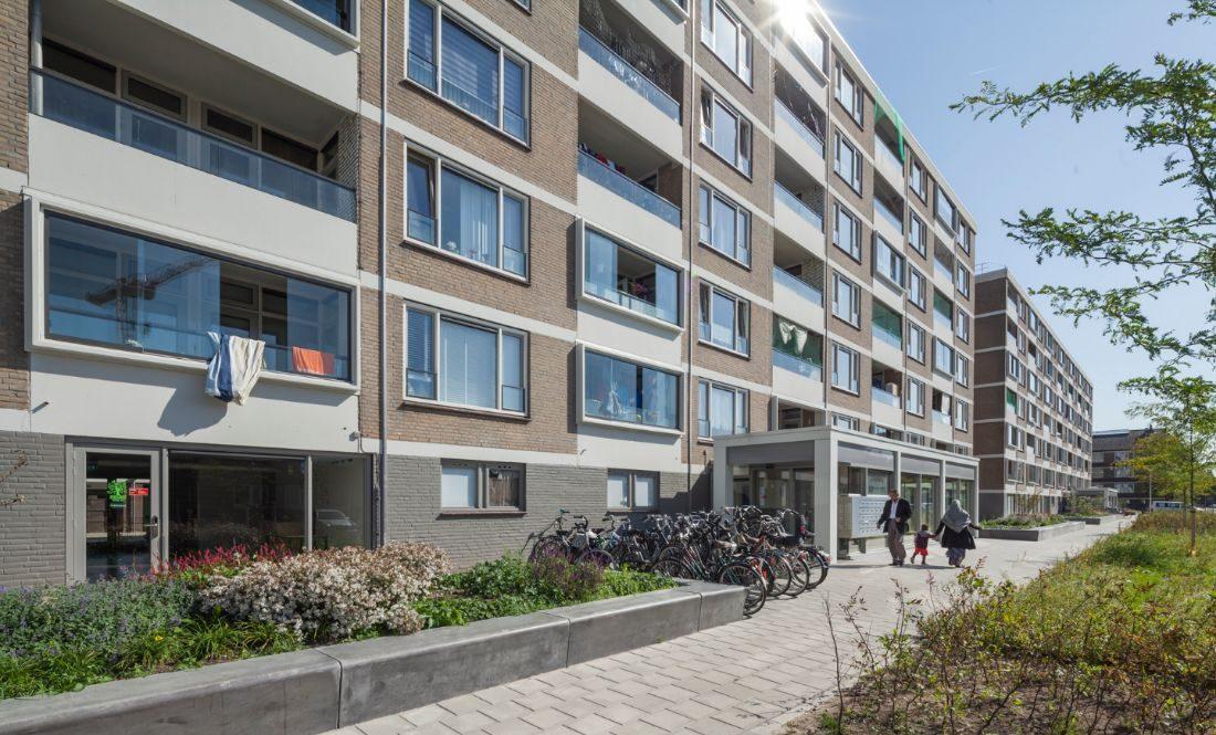 Foto van de nieuwe situatie van de schuilenburg flat in amersfoort met een beeld van de flat vanaf de parkeerplaats en een close up van de entree en de bergingen.