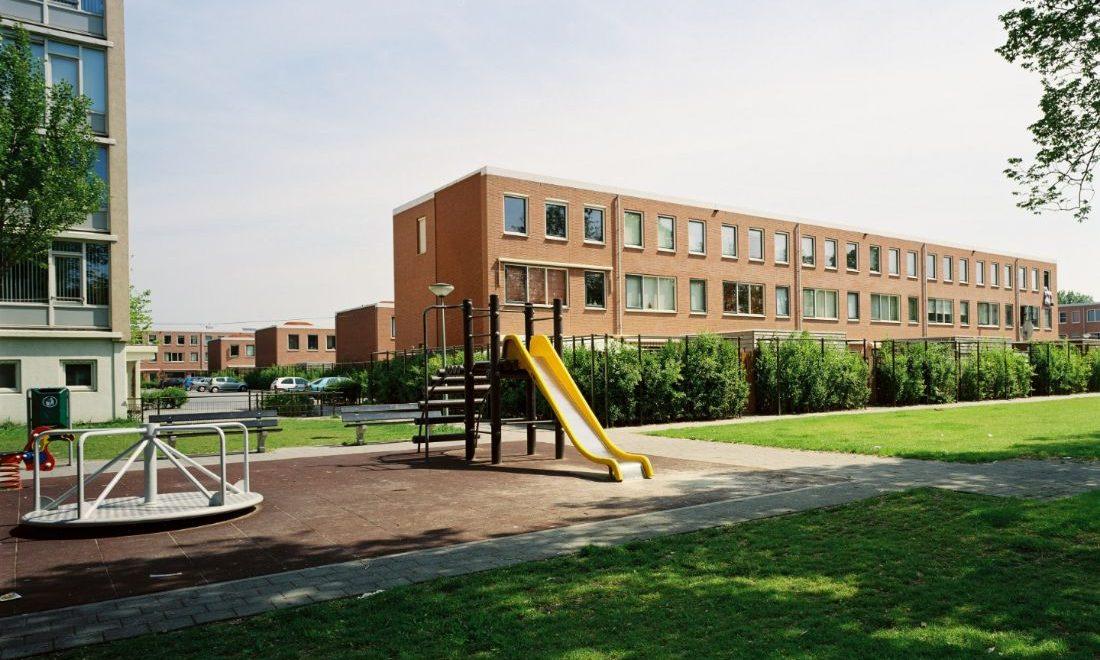 aanzicht van een van de nieuwe woonblokken in de westwijk in vlaardingen met op de voorgrond aan speeltuin en een grasveld