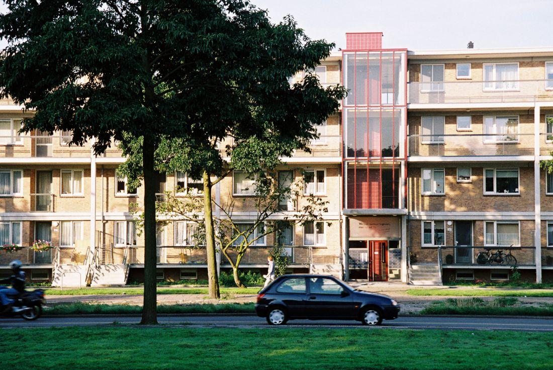 foto van de gerenoveerde portiek van de loevesteinlaan flat in het enschedelaan complex met een auto en gras op de voorgrond