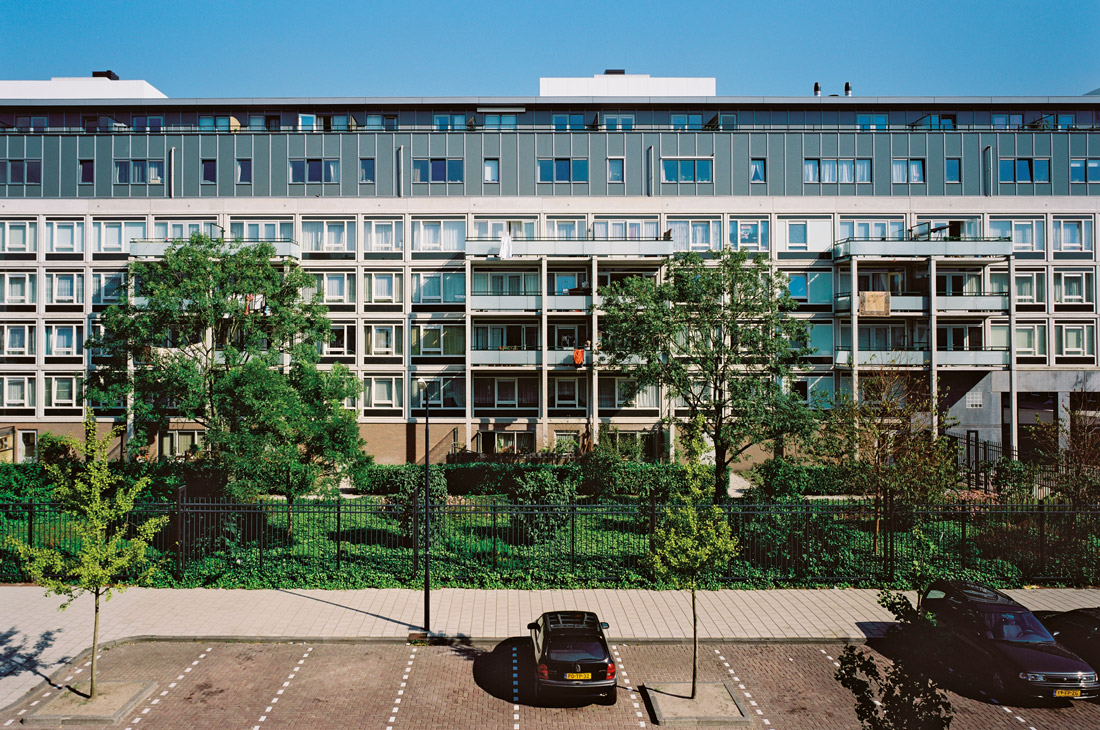 vooraanzicht complex 50 en 117 met vernieuwde gevels na de renovatie met ervoor een grote begroeide omhekte tuin en een parkeerplaats met auto's