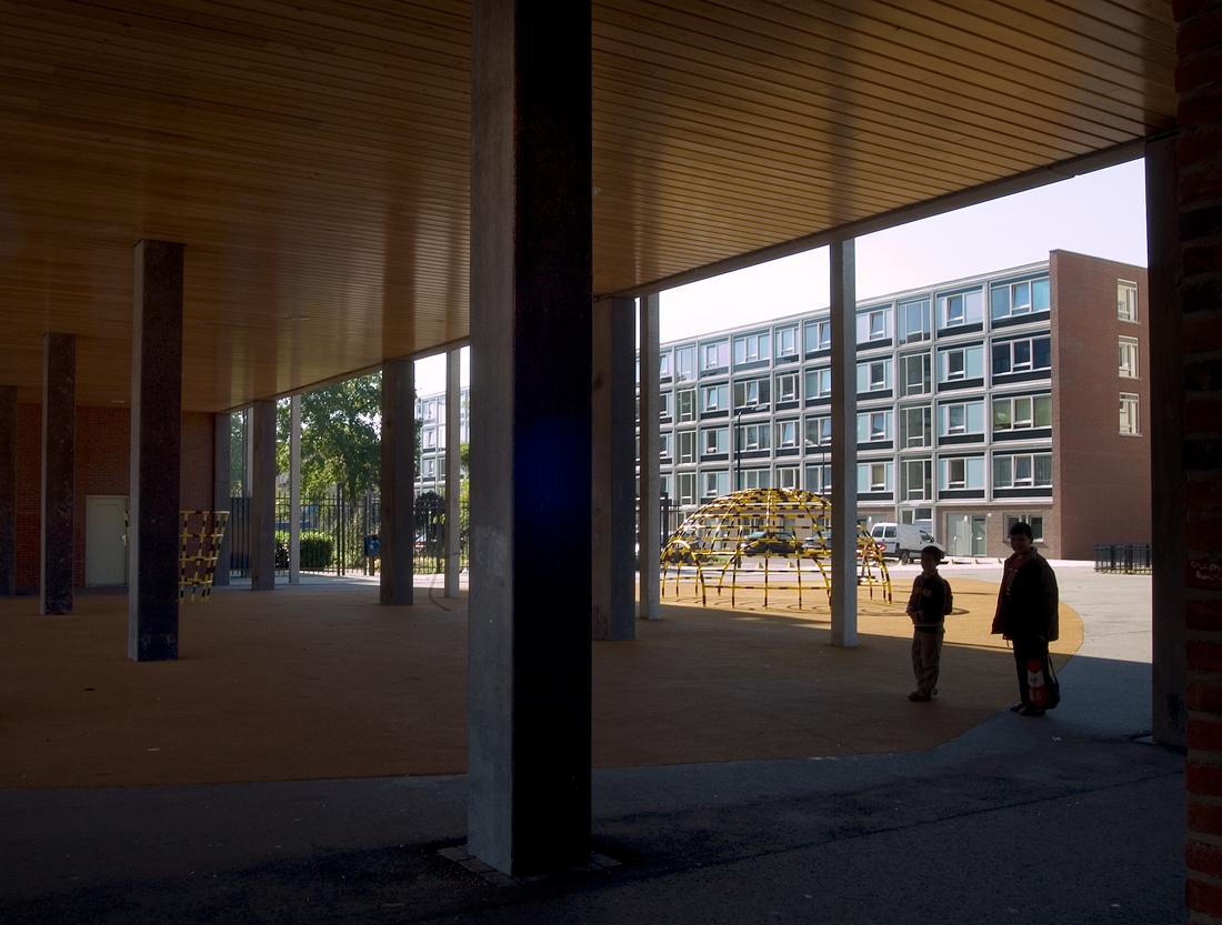 aanzicht van een ander flatgebouw in complex 50 en 117 vanuit de poort met een speeltuin ertussen en twee mensen
