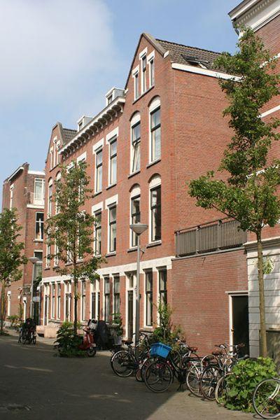 fietsen en bomen voor een huizen rij van de rechter zijkant gezien met daartussen een schuurtje