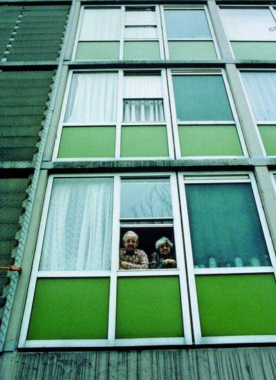 de gevel met groene details van complex 50 en 117 in amsterdam met twee ouderen kijken uit een open raam in de situatie voor de renovatie