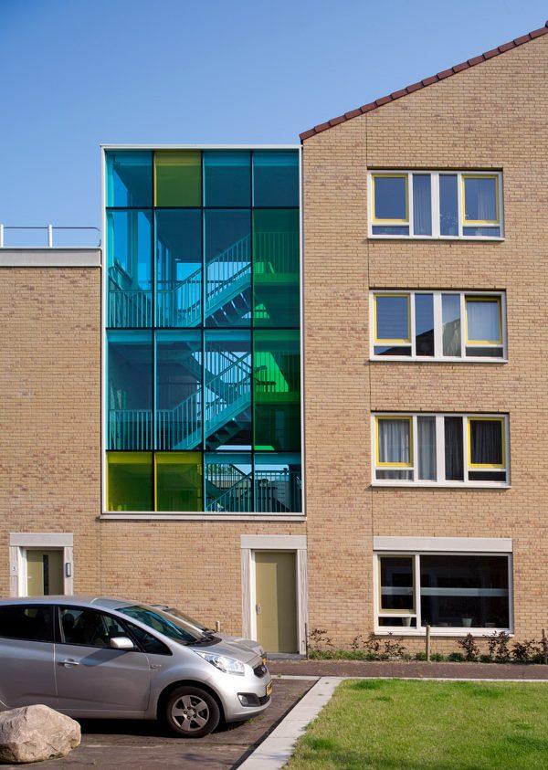 Aanzicht van de zijgevel balkons van een van de gebouwen van de nieuwbouw in het schilderskwartier in woerden met glazen wand in blauw, groen en geel