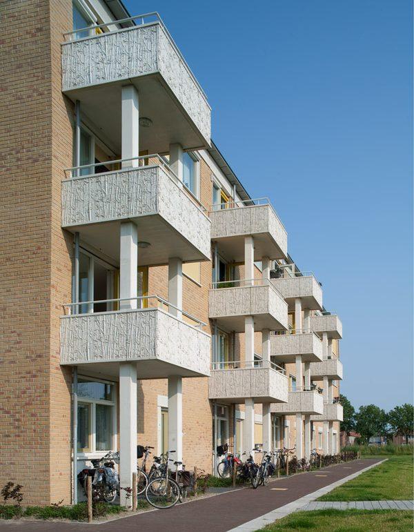 Zijaanzicht met uitstekende balkons van een van de gebouwen van de nieuwbouw in het schilderskwartier in woerden