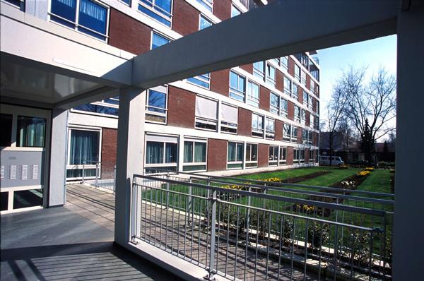 aanzicht van de gerenoveerde huize patrimonium gezien vanuit de vernieuwde entree met betonnen structuur