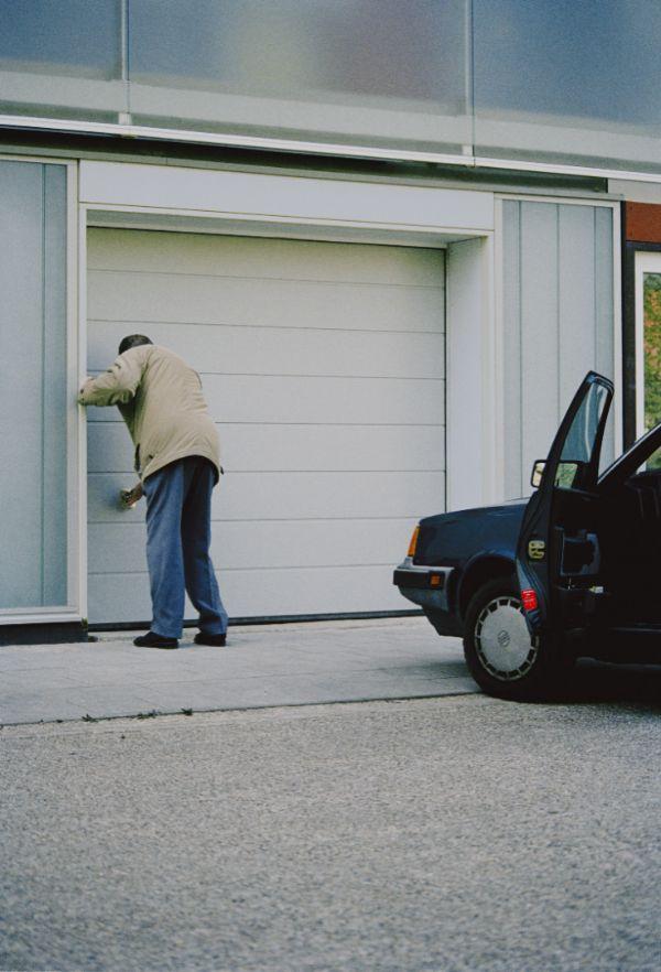 een man bij een garage deur met zijn auto aan de plint van een van de prinsenflats na renovatie in rijsiwjk