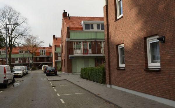 Zijaanzicht van een van de huizenblokken in de sagenbuurt in Rotterdam na renovatie met rode deuren en groene details