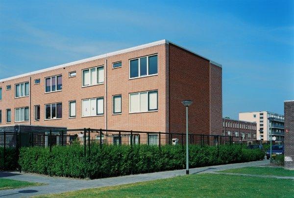 aanzicht op de achterkant van een van de nieuwe woonblokken in de westwijk in vlaardingen met zicht op de begroeide achtertuinen