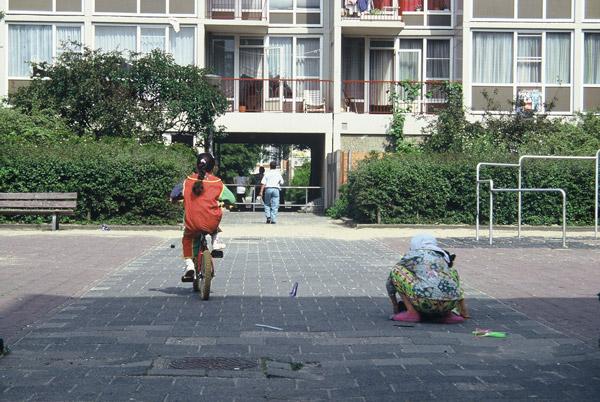 kinderen spelen op de straat en stoep met op de achtergrond de onderdoorgang van complex 50 en 117 in de oude situatie