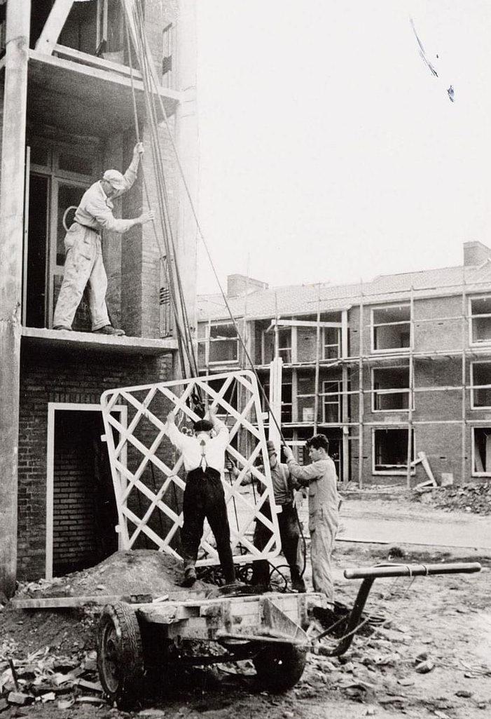 oud beeld van mannen die ene van de balkonplaten naar boven takelen aan een van de nieuwbouw woonblokken aan de gasthuislaan in amersfoort