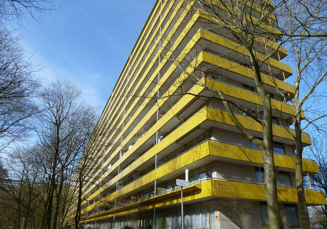 foto van de geroflat na de renovatie in zeist met gele balkons en bomen om het gebouw heen