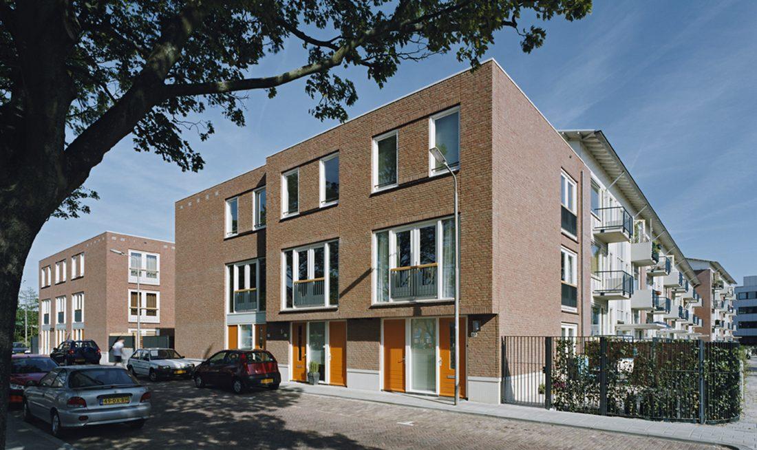 aanzicht van de nieuwbouw in het oostblok in delft met daarachter de gerenoveerde bestaande woningen en ervoor in de straat auto's
