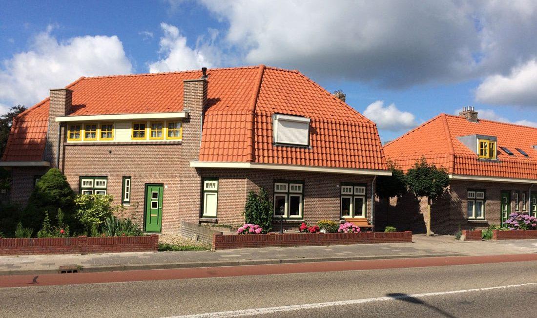 huizen aan de paul krugerlaan na de renovatie met groene deuren en gele en witte kozijnen en oranje dakpannen
