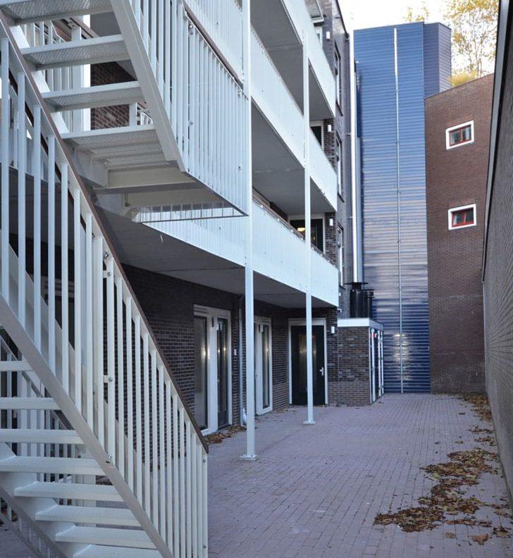 aanzicht van de binnenplaats met galerijen en trappen van het appartementencomplex hogewoerd in woerden