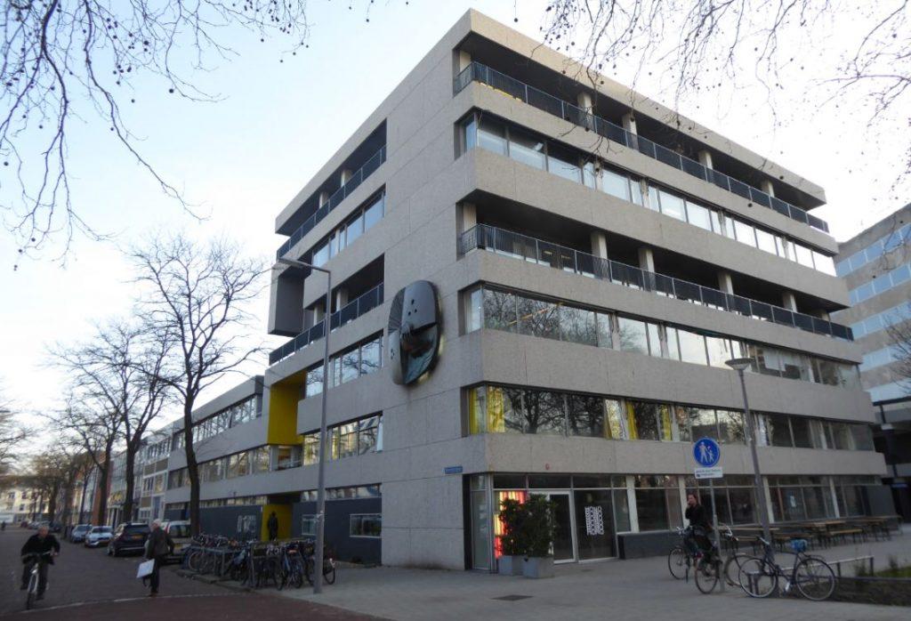 aangezicht van het gele gebouw na renovatie met fietsers en wandelaars en het beeldhouwwerk op de gevel