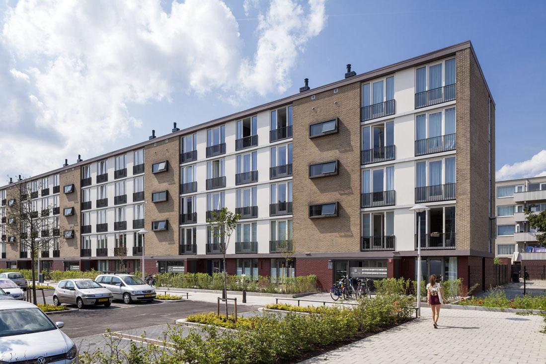 zijaanzicht van rechtsvoor van een van de flats na renovatie op het kanaleneiland in utrecht met ervoor een parkeerplaats en een buurtbewoner