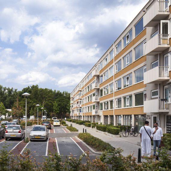 foto van een van de gerenoveerde gebouwen van kanaleneiland met gele details op het gebouw en links van het gebouw een parkeerplaats en pratende mannen