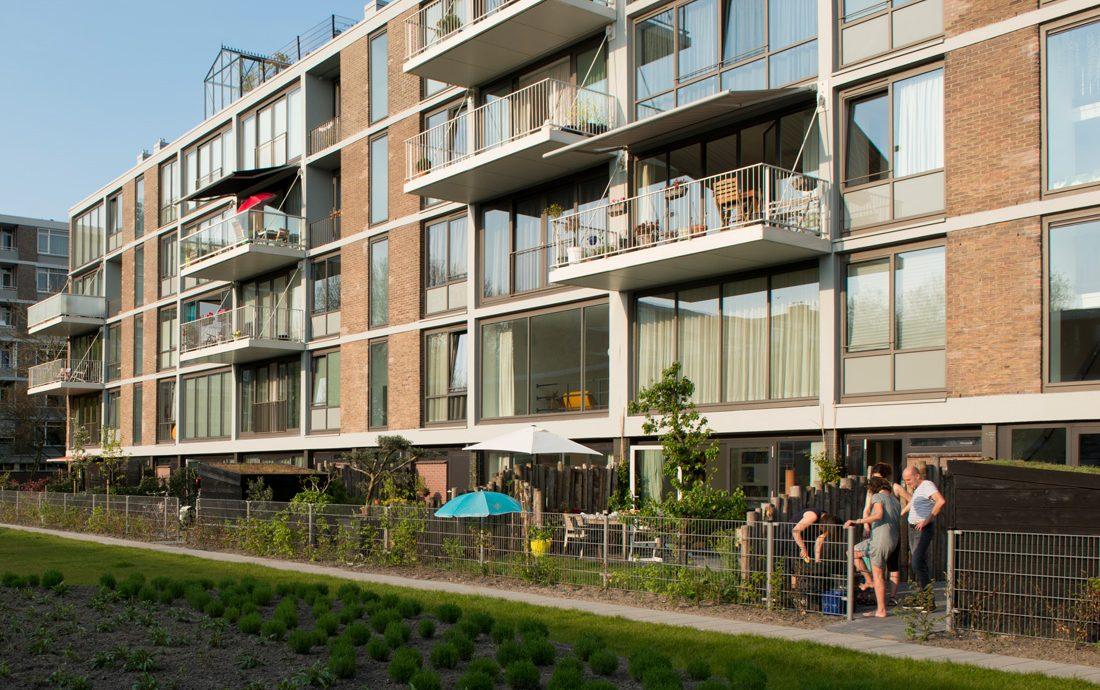 de tuinzijde ,met balkons, groen en tuinen, van de klarenstraat in amsterdam met bewoners in de tuinen