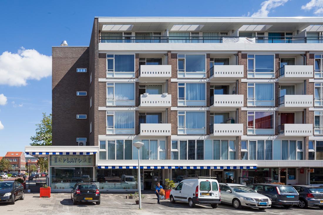 vooraanzicht van een deel van de senecaflat in amsterdam na renovatie met bruine en witte details met geparkeerde auto's en een persoon ervoor op de parkeerplaats