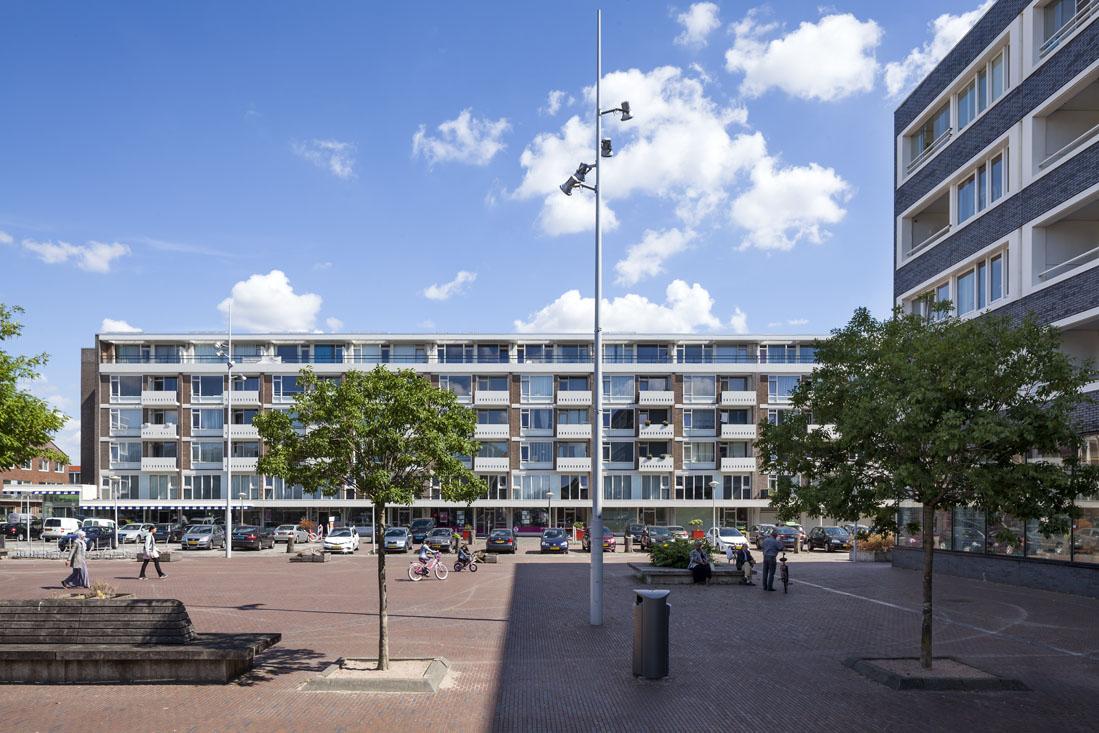 aanzicht van het plein waar de senecaflat in amsterdam aan ligt met geparkeerde auto's en buurtbewoners