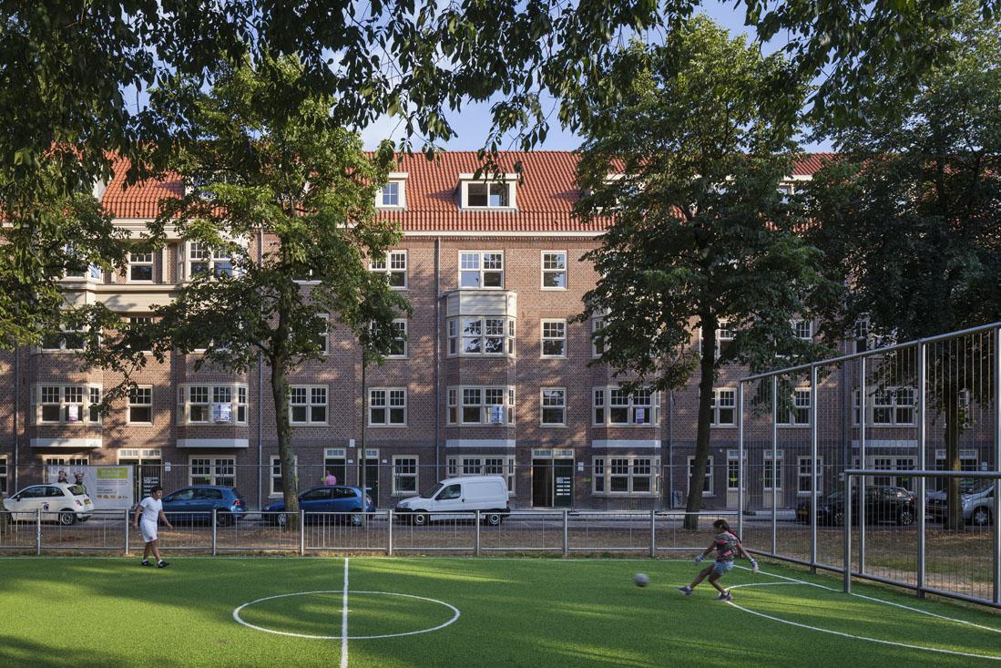 voetballende kinderen op een grasveldje voor de huizen aan de tugelaweg na de renovatie