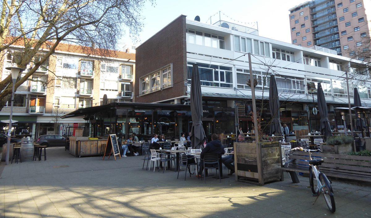 aanzicht van het cafe bokaal in rotterdam na de renovate met mensen op het terras en een fiets rechts