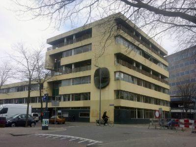 bestaande situatie van het aangezicht van het gele gebouw voor renovatie met fietsers en wandelaars en het beeldhouwwerk op de gevel