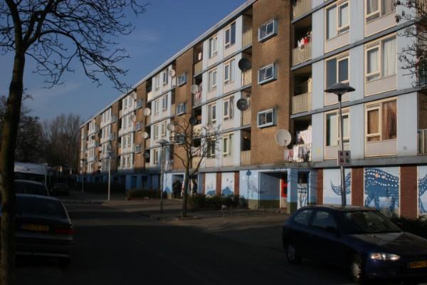 de bestaande situatie van een flatgebouw op kanaleneiland met ernaast een schutting en vuilnisbakken