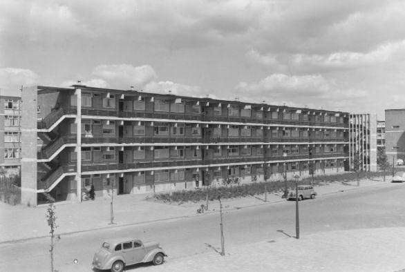 aanzicht van de oude situatie van de bakema flat in 1959 met ervoor een weg met auto's
