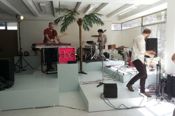 een band op verhogingen met keyboard, drumstel en microfoon en een palmboom in het midden