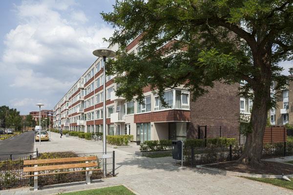 zijaanzicht van rechts van een van de flats na renovatie op het kanaleneiland in utrecht met aan de linkerkant een bankje en parkeerplaats