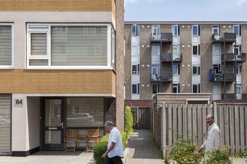 vooraanzicht van een scheiding tussen twee verschillende flats op het kanaleneiland in utrecht met bewoners wandelend