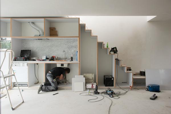 een man die een kast en trap in een aan het in elkaar zetten is in een verdere lege woning aan de klarenstraat