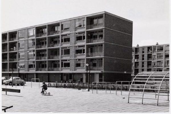 de oude situatie van de woningen aan de klarenstraat in amsterdam met ervoor een speeltuintje en een jongetje op een fietsje