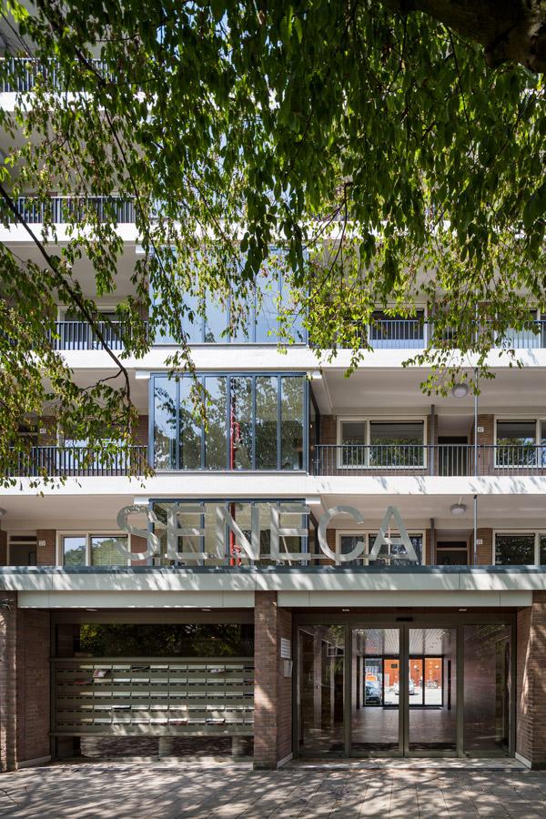 aanzicht op de vernieuwde entree van de senecaflat in amsterdam met de naam seneca groot boven de ingang en postvakken