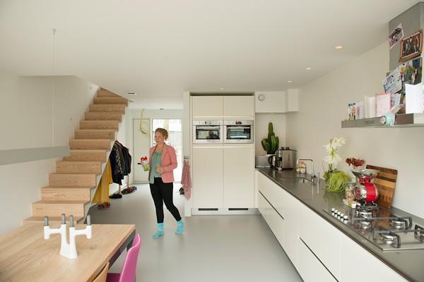 het gerenoveerde huis van de binnenkant met een witte keuken en grijze accenten