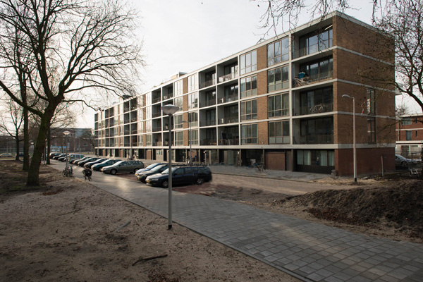 de nieuwe situatie van de woningen aan de klarenstraat na renovatie met geparkeerde auto's en mensen ervoor